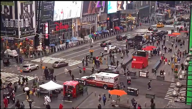 In this image taken from video, pedestrians hurry away from the scene of a shooting in Times Square on Saturday.
