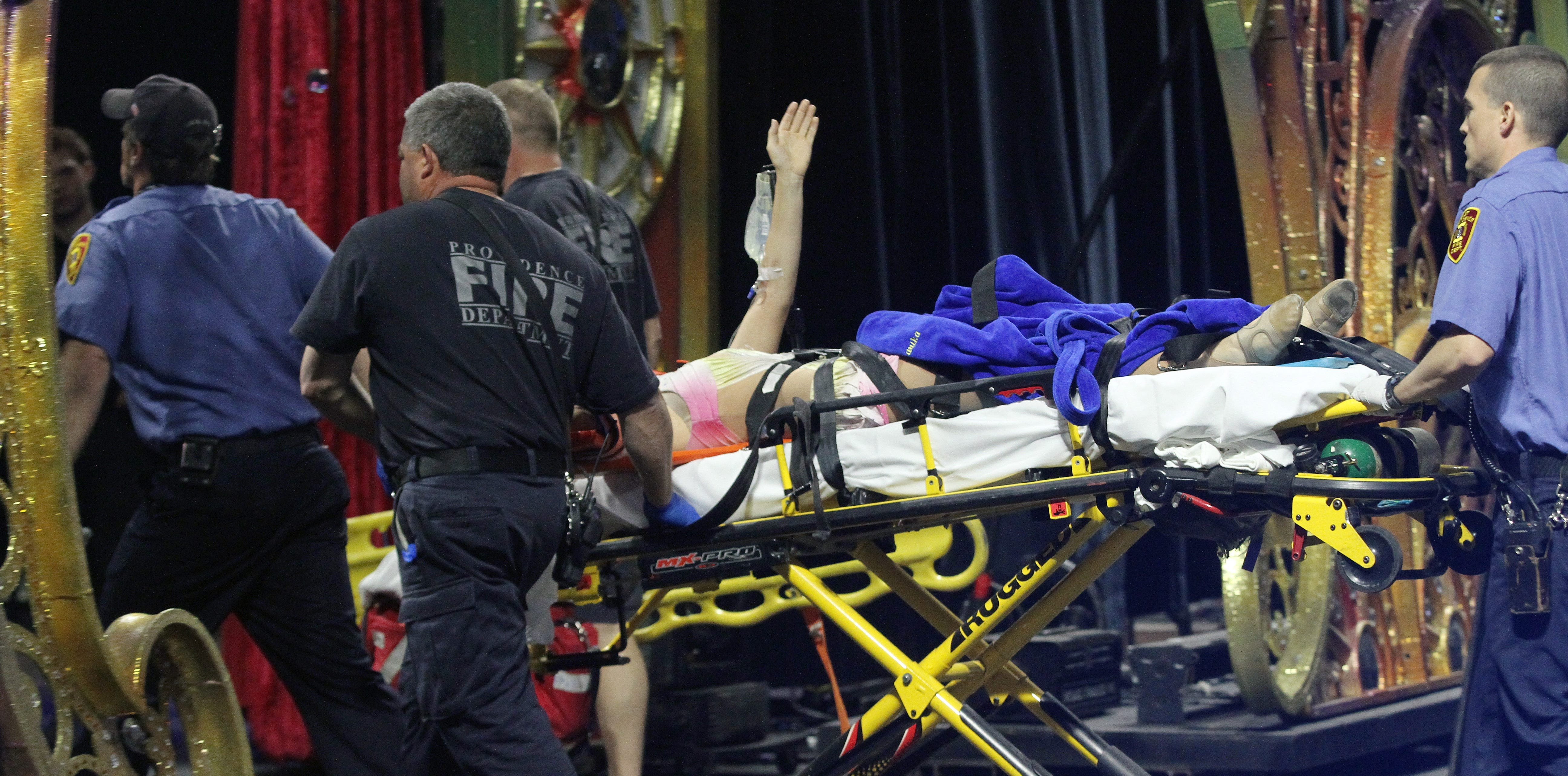 Widny Neves waves to the crowd as she is wheeled out of the Dunkin' Donuts Center after the accident.