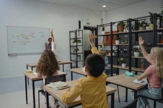 A classroom with young students raising their hands and participating in class.