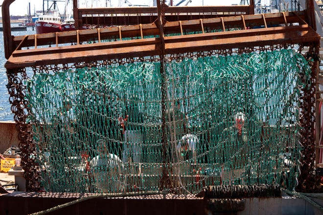 The crew of the scalloper Flavian S. are obscured by the twine top as, they fix the dredges of the New Bedford fishing boat.