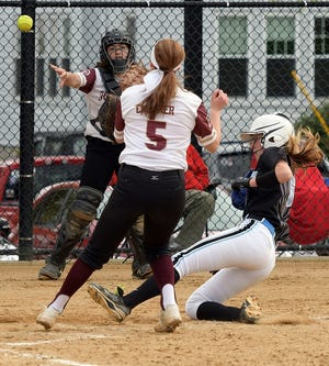 Holy Name's Abby Erickson scores on a passed ball as Doherty catcher Ava Bogosian throws to pitcher Tori Creamer during a 2019 game.