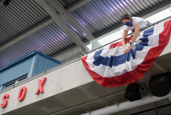 WooSox employee Hannah Butler adjusts bunting behind home plate on Monday in preparation for Tuesday's Opening Day.