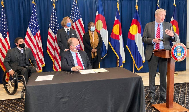 Gov. Jared Polis (foreground) prepares to sign a prison mentorship bill into law. Colorado Department of Corrections Executive Director Dean Williams (left) speaks about the impact the bill will have at Pueblo's Youthful Offender Services prison.