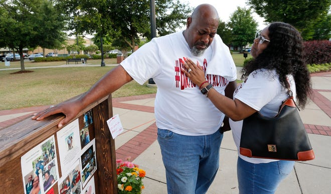 Tracy Braggs, a COVID-19 survivor, is comforted by his wife, Latonya, as he talks about his father's death from COVID-19 in November 2020. The Braggs family was attending a May memorial for COVID victims in Tuscaloosa, Alabama.