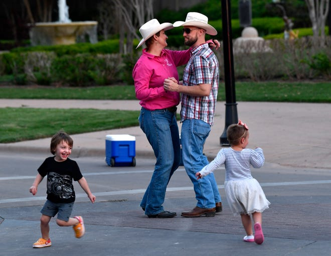 Twins Jonathan and Alanna Clark, 3, race around the Texas star as Will and Annaliese Scoggin dance behind them after Thursday's Western Heritage Classic Parade.