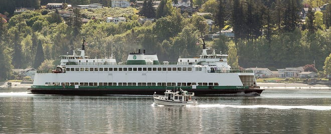 The Washington State Ferry Sealth passes a small tugboat as it heads for the Bremerton Ferry Terminal on Monday.