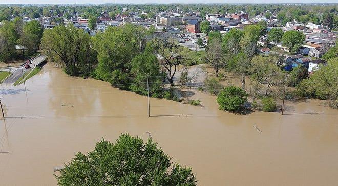 The Sandusky River spills over into Harmon Field near Water Street on Monday.