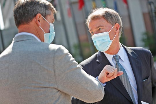 Eli Lilly and Company CEO David Ricks, left, and Mayor Joe Hogsett elbow bump after a press conference Monday, May 10, 2021 about the back-to-work plan for Lilly, at the downtown Indianapolis headquarters.