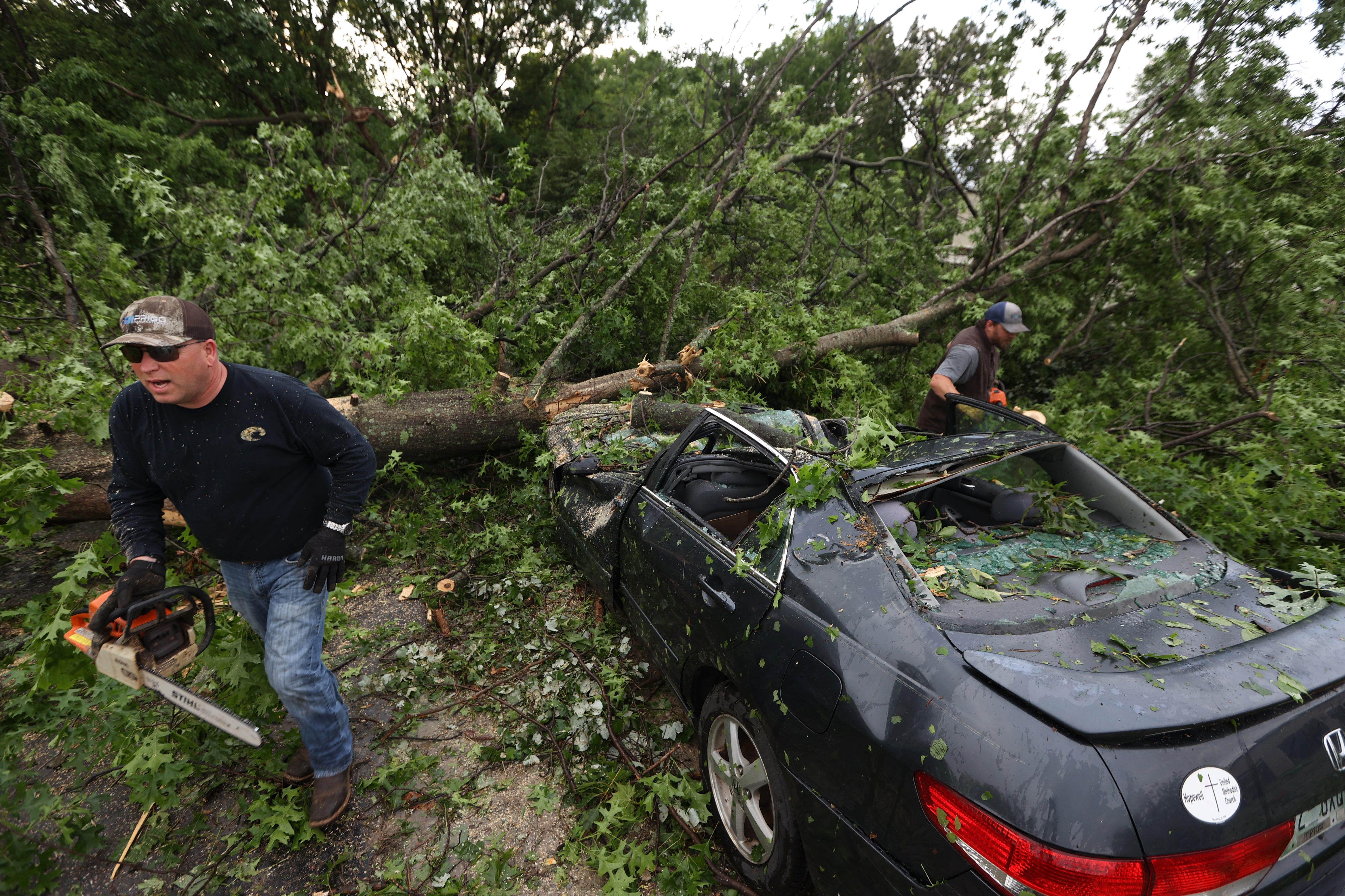 Bryan Bomar works to help cut a damaged car loose from a fallen tree on family property after a tornado touched down in Tipton County on Sunday, May 9, 2021.