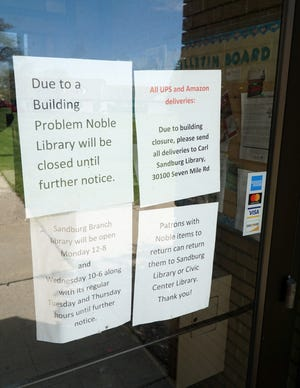 Signs on the door of the Livonia Public Library Alfred Noble Branch indicates it's continuing closure.