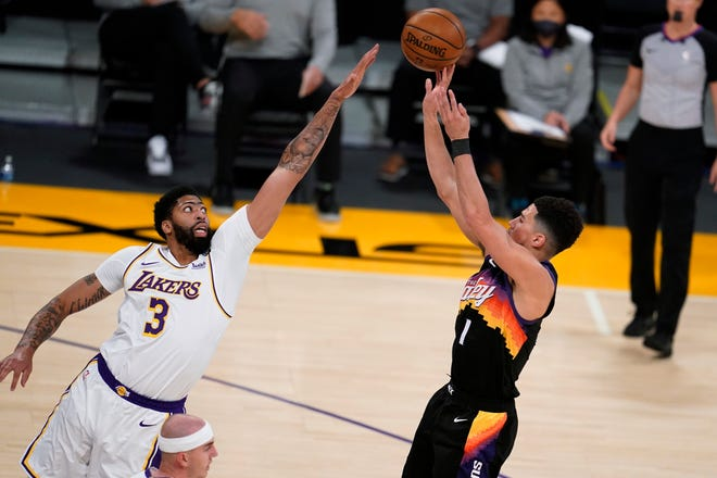 Phoenix Suns guard Devin Booker, right, shoots over Los Angeles Lakers forward Anthony Davis (3) during the first half of an NBA basketball game Sunday, May 9, 2021, in Los Angeles. (AP Photo/Marcio Jose Sanchez)
