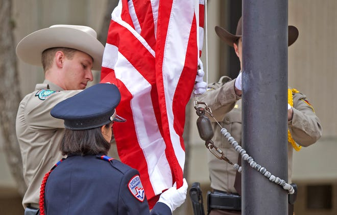 Law enforcement officers raise an American flag during a ceremony honoring National Police Week at the Tom Green County Sheriff's Office on Monday, May 10, 2021.