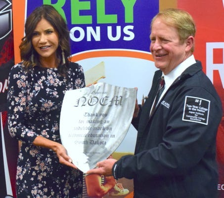 Gov. Kristi Noem, left, accepts an honorary shield from Michael Cartney on behalf of Lake Area Technical College.