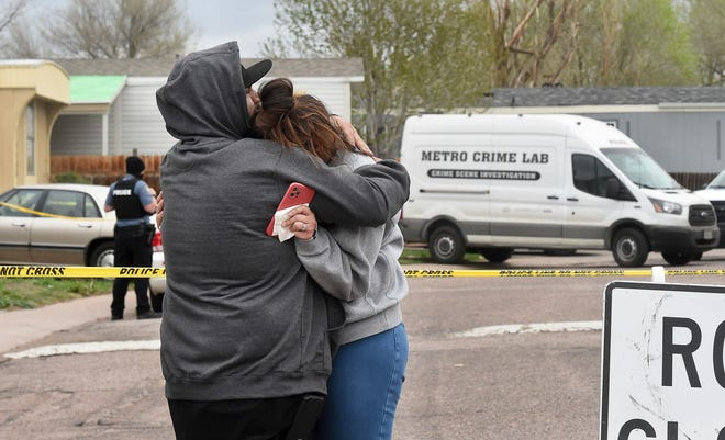 Freddy Marquez kisses the head of his wife, Nubia Marquez, near the scene where her mother and other family members were killed in a mass shooting May 9 in Colorado Springs, Colo.