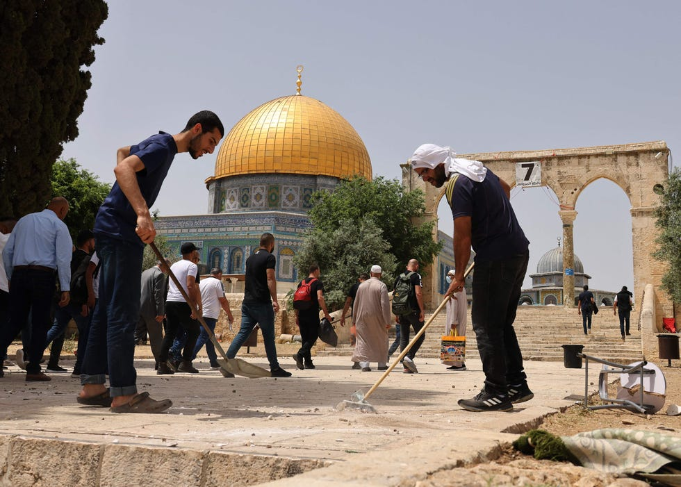 Palestinians clean the Al-Aqsa mosque compound on May 10, 2021, following renewed violence with Israeli police as an Israeli celebration of its 1967 takeover of Jerusalem risked inflaming tensions. (Photo by Ahmad GHARABLI / AFP) (Photo by AHMAD GHARABLI/AFP via Getty Images) ORG XMIT: 0 ORIG FILE ID: AFP_99N6HX.jpg