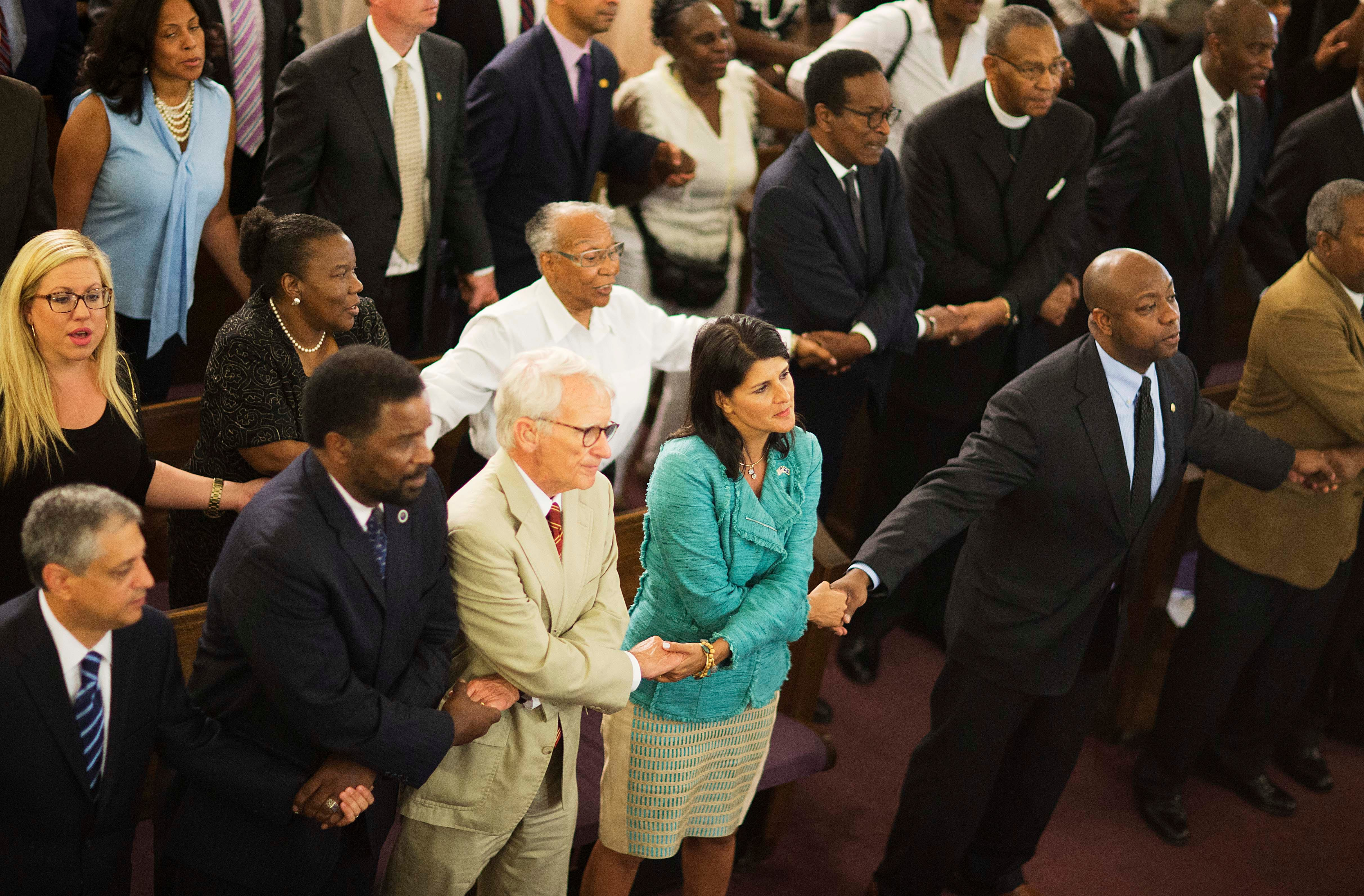 South Carolina Gov. Nikki Haley joins hands with Charleston Mayor Joseph Riley and Sen. Tim Scott, R-S.C., at a memorial service at Morris Brown AME Church for the people killed during a prayer meeting inside the historic black church in Charleston, S.C.