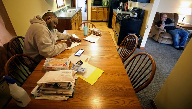 Chris Ridley fills out Community Oriented Recovery paperwork at the dining room table of the addict recovery home in Akron where he was staying in March.