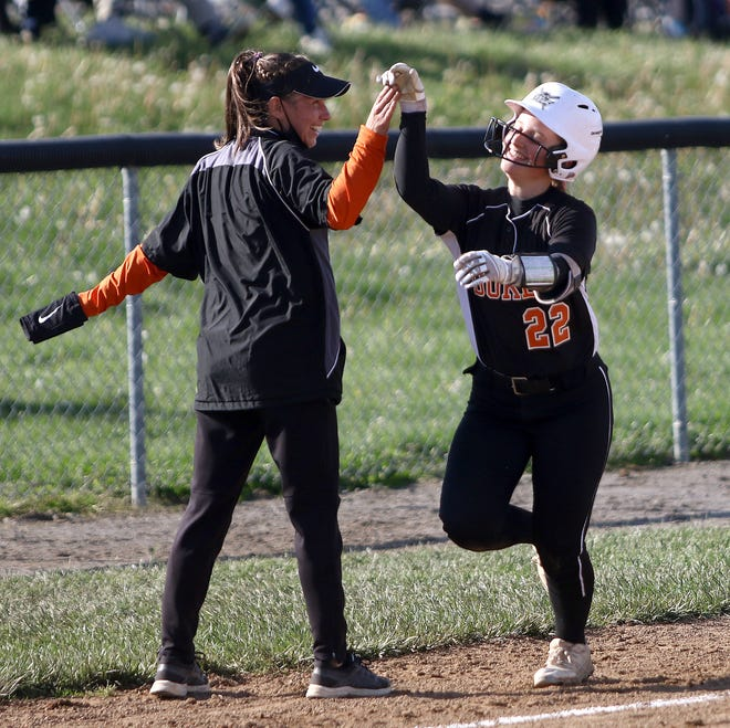 Marlington head coach Jessica Collins, left, high-fives Audrey Miller, right, as she heads towards home following a solo home run against West Branch Monday.