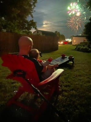 Mike Metz and his daughter, Riley, watch the 2020 Ashland Rotary July 4 Fireworks from his backyard.