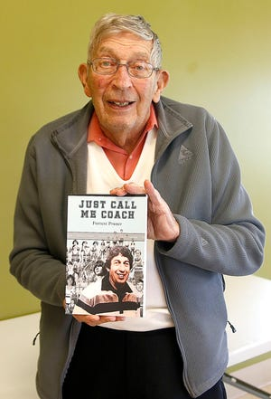 """Forrest Pruner poses with a copy of his book, """"Just Call Me Coach,"""" on Tuesday, May 11."""