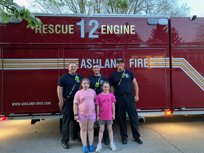 Ashland firefighters Justin Hubler (left), Tony Morris (middle) and Capt. Chad Buzzard pose with Reagan Dove, 9 (bottom left) and Dove's friend, Loxley Salmons, 8, after the firefighters rescued a bird from a tree in Salmons' yard.