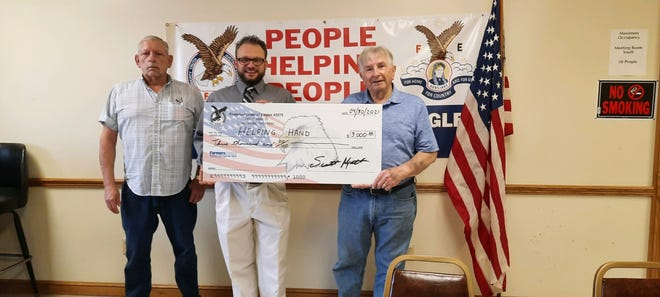 Loudonville Eagles trustees Bob Everhart, left, and Shawn Seffens, middle, present a check to Gene Heller for Helping Hand for $3,000.