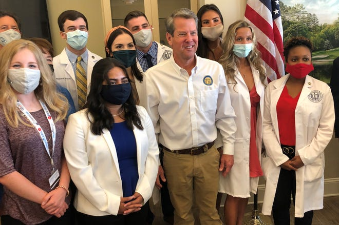 Georgia Gov. Brian Kemp poses with students and staff from the Medical College of Georgia after a news conference at Augusta Regional Airport on Tuesday.