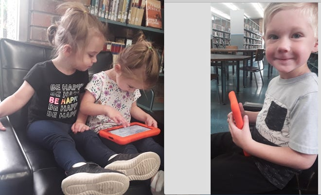 From left, Tori, Cora and Tom Byrd play with LaunchPads in the library.