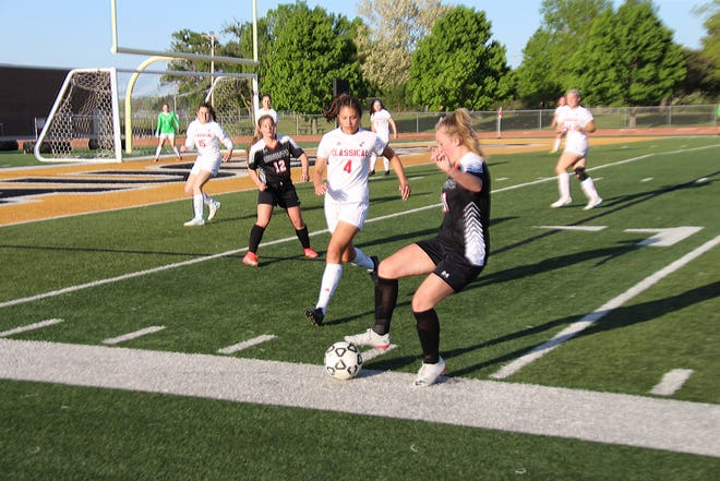 Augusta's Lauren Howard dribbles near a Wichita Classical defender in Monday's game at Augusta High School.