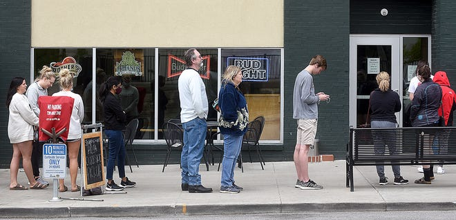 Diners stand in line outside Shakespeare's Pizza at 225 S. Ninth St. on Tuesday with some wearing masks and some not. The Columbia/Boone County health department announced its local health order will expire Wednesday without renewal. Businesses will decide if they want to continue requiring customers to wear masks, which are still recommended by health officials.