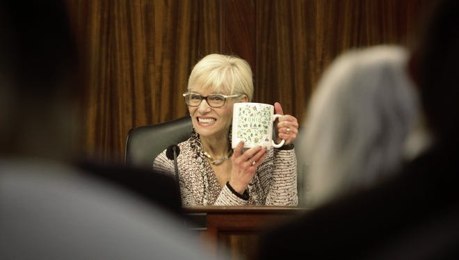 Franklin County Commissioner Marilyn Brown shows off her mug at a meeting on December 19, 2017.