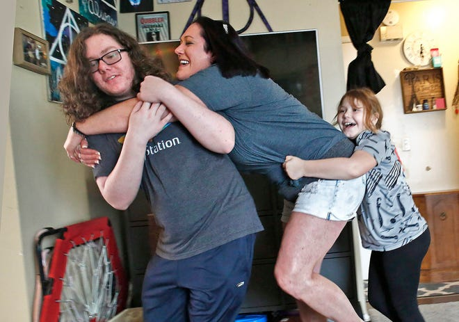 Sara Jucha is a single mom with two kids. She gave up her job to manage her children at her Gahanna home through the coronavirus pandemic. A group hug turns into a wrestling match between Sara, center; son Kasey Burns, 15, left; and daughter Lily Jucha, 8, right.