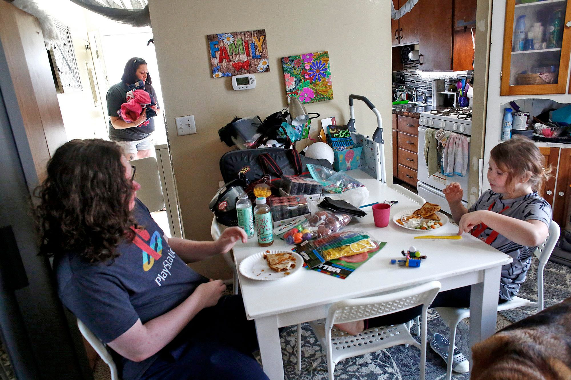 Sara Jucha puts laundry into the dryer as her children Kasey Burns, 15, left, and Lily Jucha, 8, eat lunch.