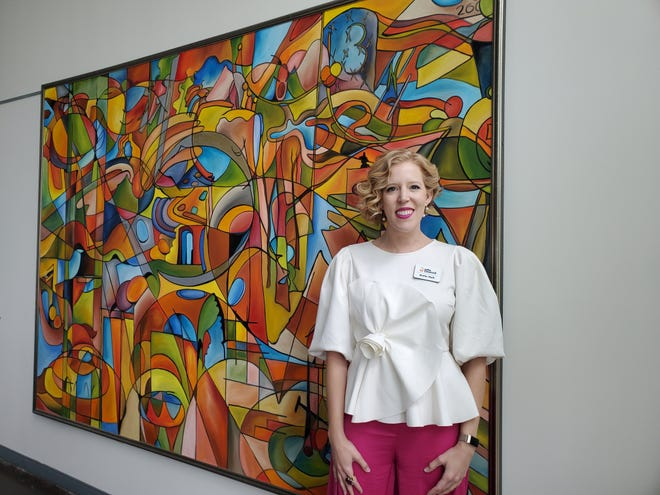 Davidson County native Katie Hall was recently named the Chief Advancement Officer for the Arts Council of Winston-Salem and Forsyth County. Here, she stands in front of a Nicholas Burton Bragg painting at Hanesbrands Theatre in Winston-Salem, where the council is headquartered.