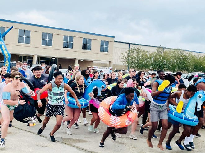 East Ascension High School seniors celebrate the traditional pond jump across from the Gonzales campus.