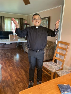 Rev. Arnel Lagman, shown with two rosaries he made, celebrated a mass with Denise Sagona and her neighbors. Sagona made a thousand rosaries to be sent to the Philippines.