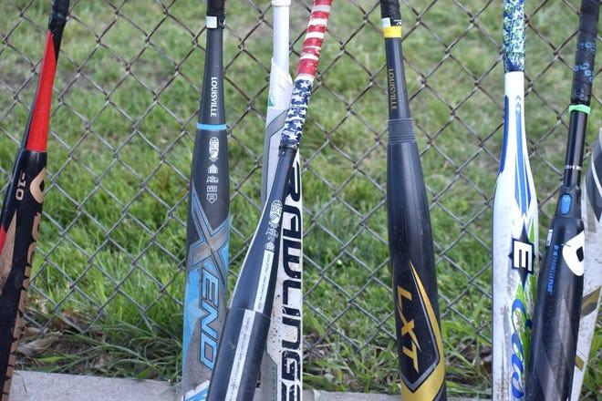 Dugout bats against fence