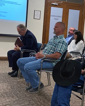 Todd Thompson and his wife Sherry sit behind Assistant Grayson County District Attorney Craig Price and IT Director Rob Crow at Tuesday's meeting where commissioners named Thompson to the GCRMA. (Jerrie Whiteley / Herald Democrat).