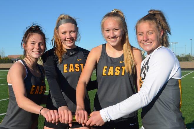 Zeeland East's 4x400 relay consists of Kaleigh VanDeWege (left), Katie Klein, Emily Macina and Paige Westra.