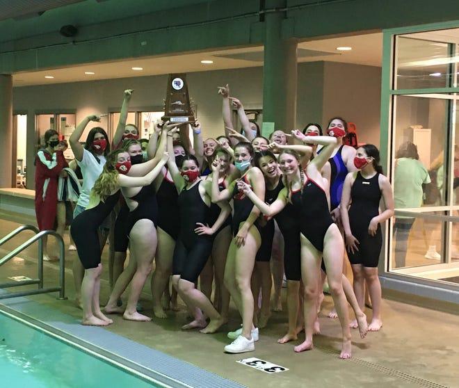 Shown is the Lansing women's swimming team celebrating its fourth-straight conference championship Monday at Turner High School.