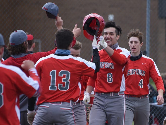 Ethan Brickner (8) of Bedford is greeted by his teammates after hitting a grand slam in the first inning against Monroe Tuesday. Bedford went on to win 14-3.