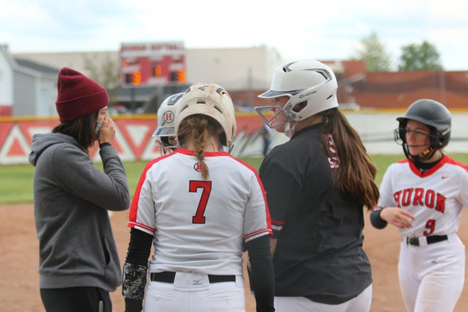 New Boston Huron softball coach Tedi Belisle has an offensive conference with her players during a 10-run first inning against Airport Monday.