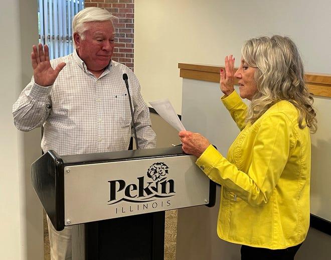 Pekin City Clerk Sue McMillen administers the oath of office for Pekin City Council member Dave Nutter.