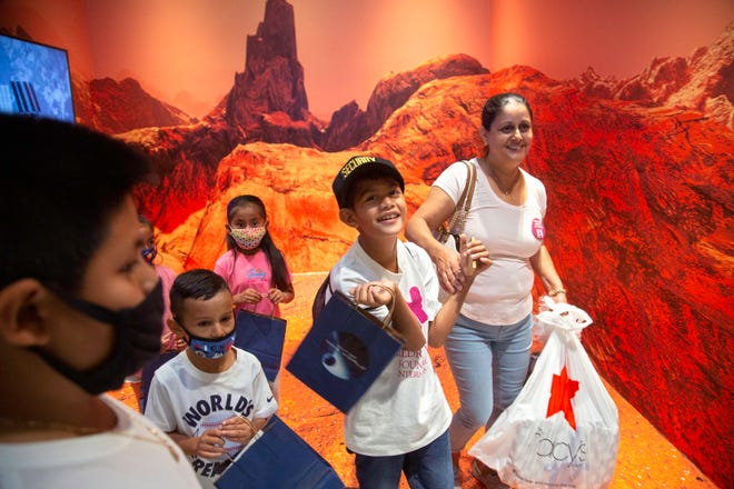 """Jesus Orozco-Vasquez, a 10-year-old with high-risk leukemia, gets a VIP experience as he visits """"Out of this World"""" during his trip to The Gardens Mall through the Children's Wish Foundation Tuesday, May 11, 2021. With Jesus is his mom, Isabel Orozco-Vasquez, and cousins at the Kennedy Space Center Visitor Complex immersion experience.  He also received a shopping spree complete with a police escort and lunch at Shake Shack."""