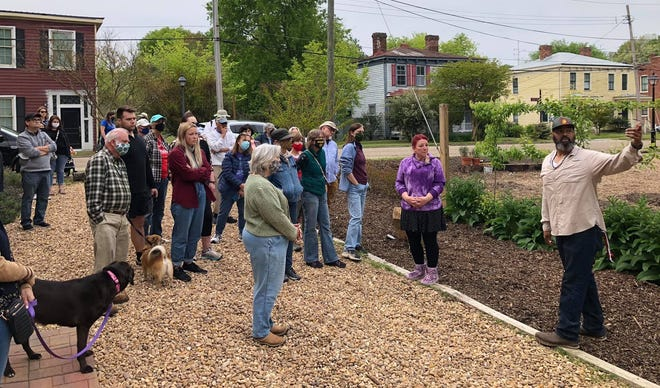 Urban farmer Marco Thomas explains his natural farming technique to tourists during the Historic Petersburg Foundation Grove Avenue Spring Walking Tour in Petersburg on April 24, 2021.