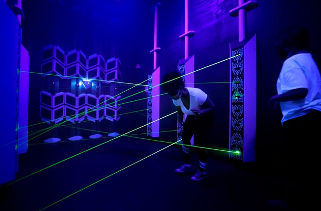 Alex DeLorenzo and Rylie Auctil try their hand against the laser beams in TimeZone's Server Heist portal.