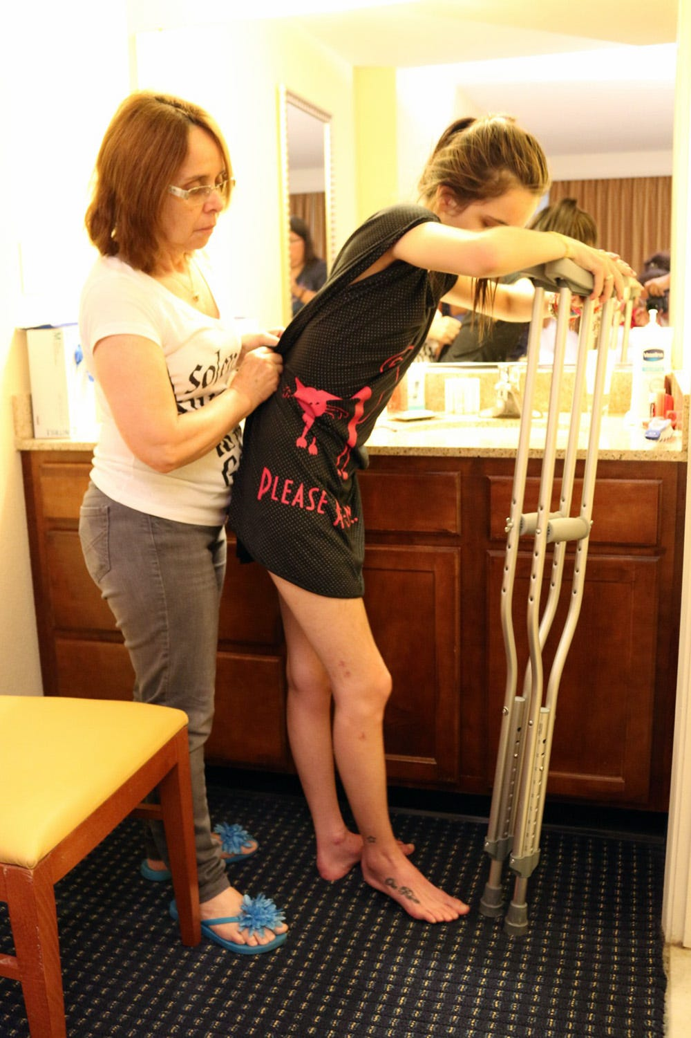 Stefany Neves, right, is assisted by her mother, Eliane Neves, at the Boston hotel where she stayed while undergoing outpatient physical therapy.