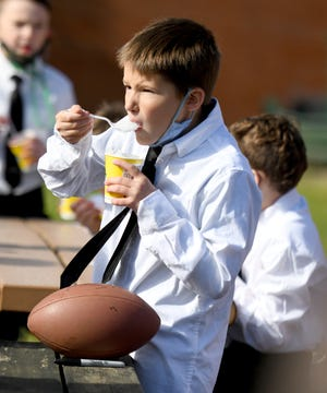 Middlebranch Elementary School third-grader Luke Shreffler is treated to a snack from Cleveland Browns tight end Harrison Bryant, who was on hand at the school Tuesday to pass out treats from Kona Ice truck to celebrate the end of the year for the Guys with Ties program.