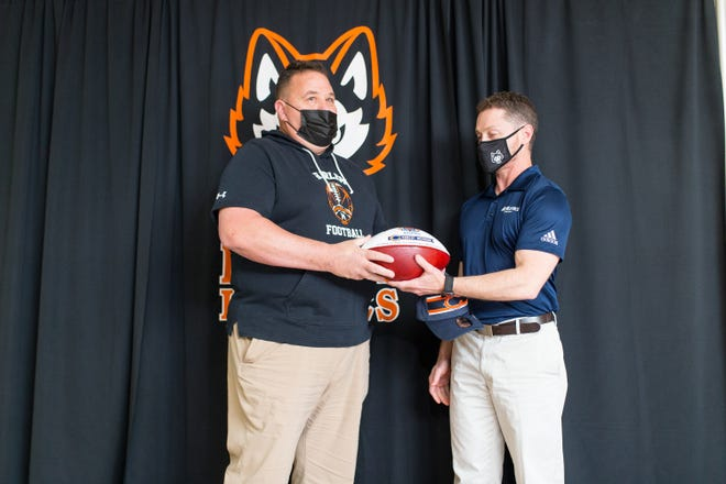 Harlem High School athletic trainer Jason Lubben, right, presents a commemorative football to football coach Bob Moynihan during a presentation Tuesday at Harlem High School naming Moynihan the Chicago Bears' Illinois state high school football coach of the year.