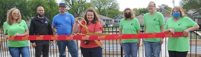 Karen Couch, executive director for the Salina Emergency Aid Food Bank, cuts the ribbon with the food bank staff members and Jason Graves, K-State Central Kansas district horticulture agent, to mark the completion of the renovations to the community garden located behind the Salina Emergency Aid Food Bank 255 S Chicago St., on Tuesday morning.